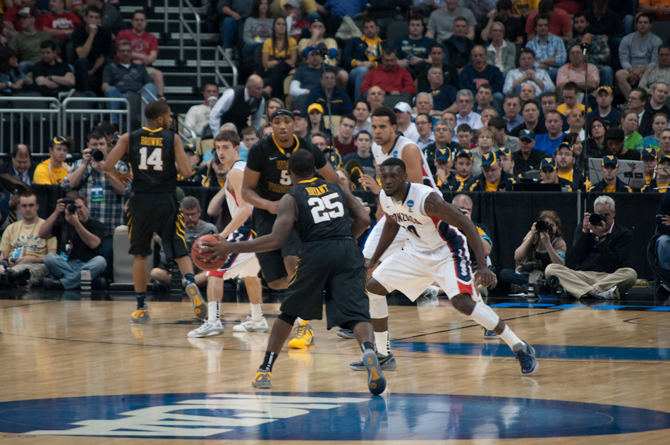 Darryl Bryant (25) of the West Virginia Mountaineers passes to his teammate Kevin Jones (5), while Gonzaga forward Guy Landry Edi (10) guards him.