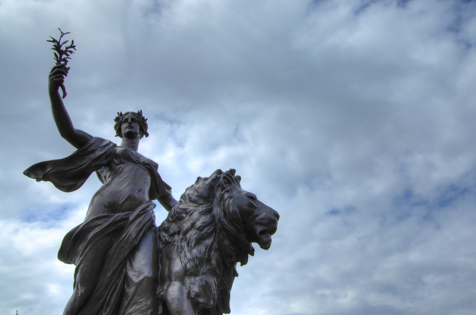 On the northeast corner of the Victoria Memorial, stands this sculpture, meant to represent the peace that Victoria brought to the Empire. The woman holds an olive branch, guarded by a lion which has long been a symbol of England. The shot is composed in HDR.