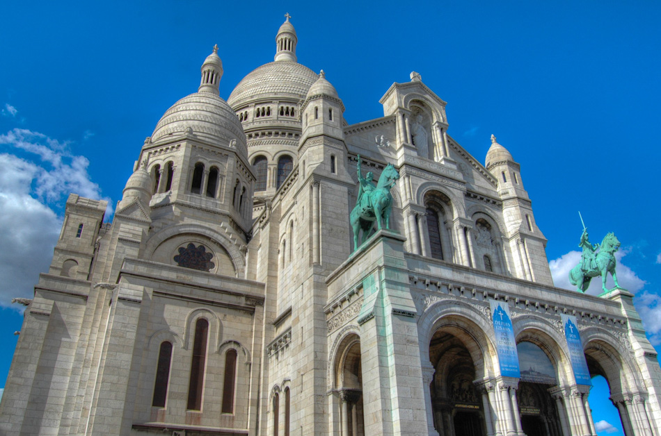 The Basilica of the Sacred Heart - or Basilique du Sacré-Cœur - in Paris, France. Shot in HDR, the image shows the dominating domes of the cathedral, which can be seen for miles around Paris, as it sits on the highest point in Paris, Montmartre.