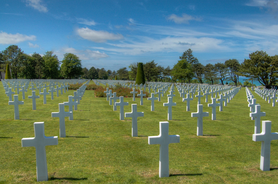 A shot of the immaculately-kept American cemetery, on Omaha Beach, Colleville-sur-Mer, Normandy, France. The graves of over 2,000 American soldiers overlooks the Omaha Beach where many of them fell during D-Day, June 6, 1944. The line of ivory crosses seen here seem to go on forever, interspersed with a Star of David, to mark those of Jewish heritage (a star can just seen just right of image centre).