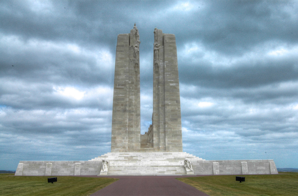 "The Canadian National Vimy Ridge Memorial, shot in HDR, as seen from the rear, while approaching from the parking lot. The two figures at the foot of the memorial are the two aforementioned ""Mourning Parents"", the male on the right, the female on the left. The ridge commands the surrounding areas and the views from the top show the French countryside in all its splendor."
