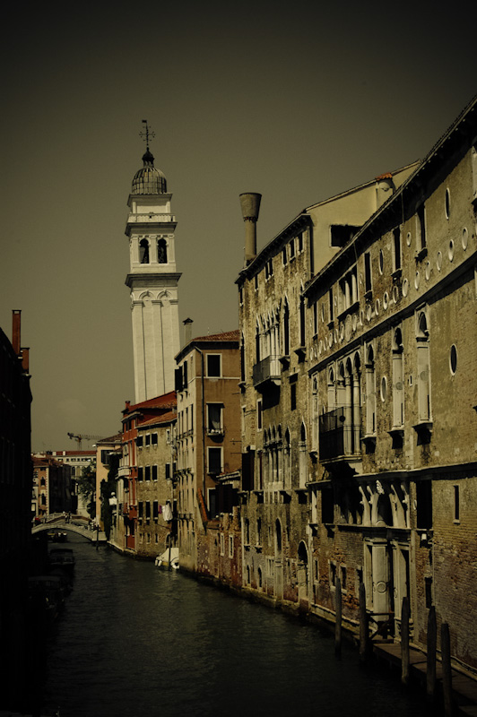 A canal and river-road in Venice, Italy. The image is dominated by the church bell tower, just left of image centre.