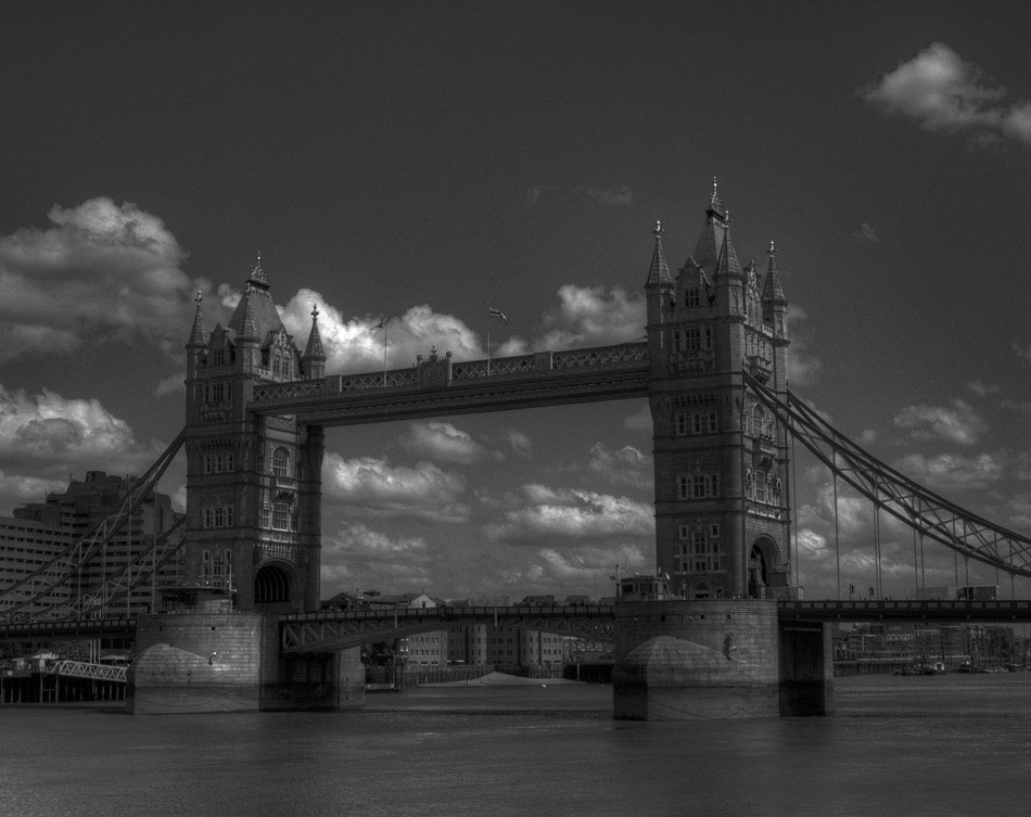 "The iconic Tower Bridge – not ""London Bridge"" – is shown here in a black and white HDR shot. Completed in 1894, the bottom roadway opens vertically to allow large ships to pass on the River Thames, while still allowing pedestrian access across the upper walkways. Currently, the upper walkways are a public exhibit, showcasing the history of the bridge, it's construction and the massive engines which make it run."