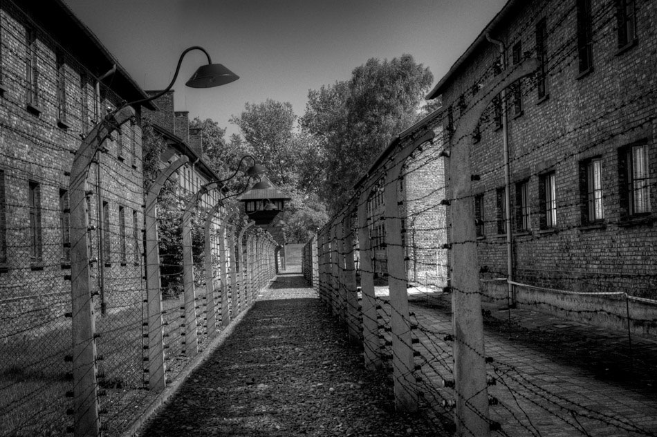 When the Auschwitz I camp was active, the double-fence seen above would have been electrified with over 10,000 volts. One of the perimeter guard towers can be seen in the background, with the rear of cell blocks seen to the right. The Auschwitz-Birkenau State Museum installed public-education exhibits in several of the cell blocks seen here; one exhibit highlighted the sheer volume of Zyklon B gas canisters discovered at the site; another displayed the long hair of women and children, cut from their bodies post-mortem. The latter was especially disturbing, especially to Jamie, who had to leave the building.