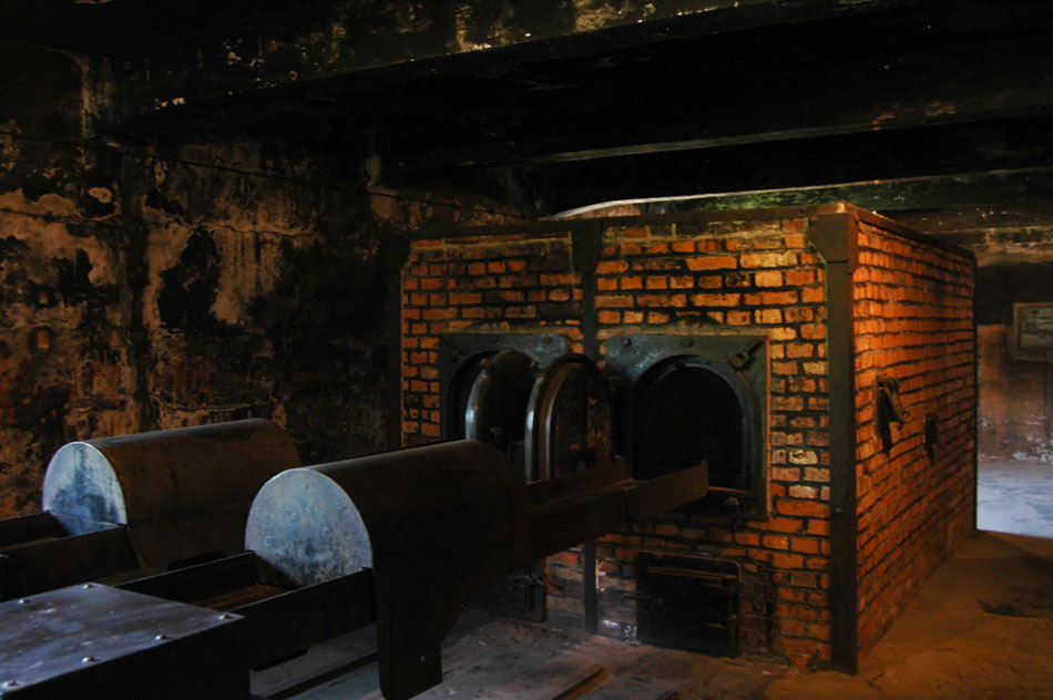 "One of the brick ovens, used for cremating the remains of victims. While touring through the Auschwitz I crematoria, the room adjacent to this was the ""shower room"", so-called because fake shower heads were installed to conceal it's true purpose. Once the intended victims were inside the shower room, the room was hermetically sealed and Zyklon B was poured in from holes in the ceiling. Once dead, the victims' bodies were transported to this room to be cremated. Take note of the rails in front, on the floor, so that the trolleys containing the bodies could be transported easier. Although several parts of the tour were especially disturbing, seeing the raw efficiency with which the Nazis approached this task was bone-chilling."