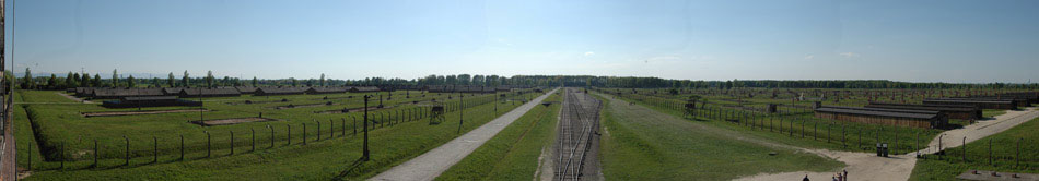 Taken from the guard tower at the front of the camp, the 180° panoramic image depicts the massive size of the Auschwitz II camp site. Housing, at its peak, nearly 100,000 prisoners, the former camp site is the size of a small village. To the left and right, the remains of individual prisoner barracks can be seen. In the distance, to the right, the remains of chimneys – two chimneys equals one building – can also be seen. Other details of the image include the main tracks (center), electrified fences (front-left and front-right) and the forest (center-top) where prisoners were shot and buried before the advent of gas chambers.