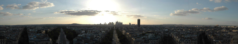 "Standing atop the Arc de Triomphe provides one of the best 360° views of Paris. The above panorama, one of my other favourites shot on this trip, shows the view facing West, highlighted by the silhouettes of ""New Paris"" in the distance. Five of the twelve avenues that meet at the Arc are visible in the photograph. And as we saw, twelve avenues arriving at the same point makes for some fun traffic patterns. The building that appears to be a transparent square in the distance of image center is La Grande Arche de La Défense. Accessible from the Arc de Triomphe via a direct Metro line, La Grande Arche was running a marathon around it when we arrived. Coupled with the broken elevators, we did not stay long in the La Défense area."