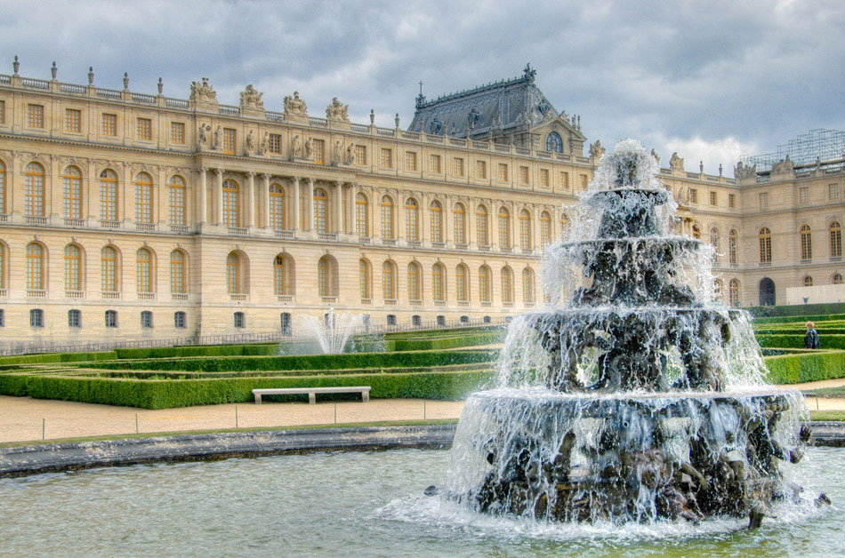 A waterfall fountain on the north end of the gardens grounds. The north wing of the Palace of Versailles is visible in the background, showcasing its yellow and gold stonework and accenting.