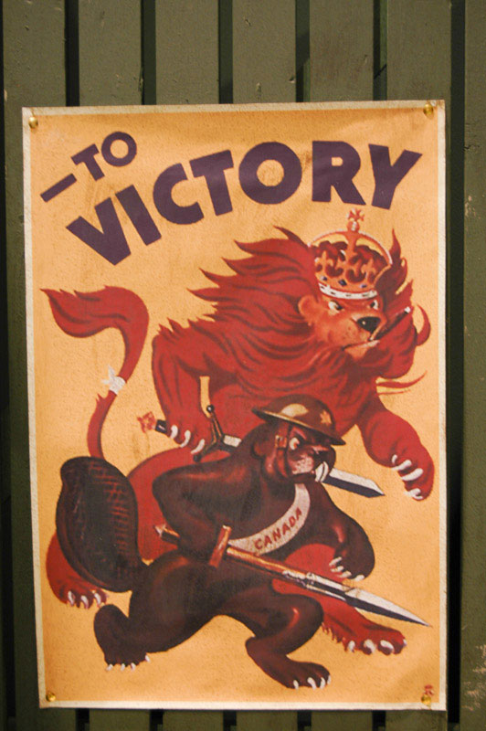 "This poster was on display at the Juno Beach Center, in Normandy, France. When Canada joined the way in 1939, many still considered England the ""Mother Country"", represented by the lion in the background. The subtle symbols are what make this poster for me: the lion has a cigar (an obvious reference to Churchill, often called ""The Last Lion""); the lion is wearing a regal crown; the lion is carrying some type of broadsword, while the Canadian beaver looks to be holding some sort of bayonet; the relative size of each, with the lion being bigger and more menacing than the beaver; and finally, the small field dressing on the lion's tail."