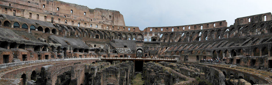 The ancient Colosseum of Rome is one of the most recognizable landmarks in the world. Seen here in a panoramic shot from its western edge, the tunnels, walkways and stone pillars that supported the ancient floor of the arena can be seen below. Remnants of the seating can be seen up each side of the massive structure.